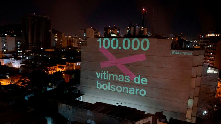 "TOPSHOT - A projection on a building honouring the 100,000 victims who died of the novel coronavirus COVID-19 in Brazil reads ""100,000 Victims of (Brazilian President Jair) Bolsonaro"" as the country became the second in the world to pass the grim milestone, in Botafogo neighbourhood in Rio de Janeiro, Brazil, on August 8, 2020. - Just a day after Latin America and the Caribbean became the hardest-hit region in the global pandemic, Brazil reported a total of 100,477 fatalities, joining the United States as the only two countries to surpass the six-digit death mark. (Photo by Mauro PIMENTEL / AFP) (Photo by MAURO PIMENTEL/AFP via Getty Images)"