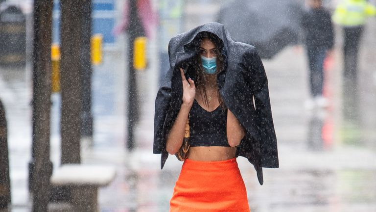A shopper gets caught in a heavy downpour of rain on Oxford Street, London, as sunshine and showers are forecast for much of England and Wales on Saturday, with temperatures expected to hover around 22C (71.6F).