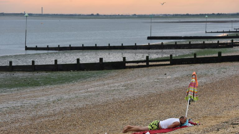 SOUTHEND-ON-SEA,  ENGLAND - AUGUST 07: A man sleeps on the beach as the sun sets in the evening on August 07, 2020 in Southend on Sea, United Kingdom. Parts of England are enjoying a three-day heatwave with temperatures set to reach up to 38 degrees centigrade in the South East. (Photo by John Keeble/Getty Images)