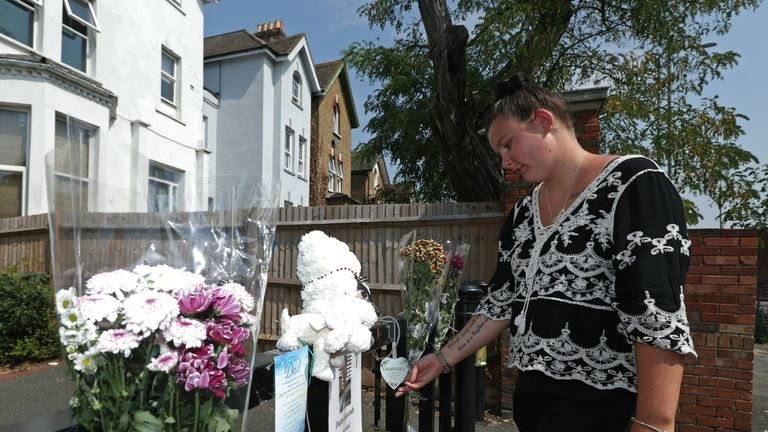 Hollie Edwards, the daughter of Dean Edwards, looks at tributes for her father at Betts Park in south London, as police renew an appeal for information over Dean's murder. Edwards, 43, was shot in the back of the head while leaving Betts Park in Penge in July.