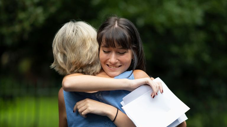 SWANSEA, WALES - AUGUST 13: Holly Cuttiford hugs her mum after receiving  her A Level results at Ffynone House School on August 13, 2020 in Swansea, Wales. Thousands of students in Wales receive their A-level grades today, amid major last minute changes to results which will see pupils promised the grades awarded to them will not be lower than their earlier AS results. Exams were cancelled due to coronavirus with grades being calculated using teachers' estimates and a formula to standardise results across schools. (Photo by Matthew Horwood/Getty Images)