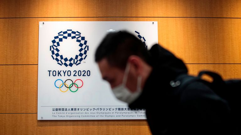 A reporter walks past a logo of the Tokyo 2020 Olympic Games after a press conference at the Tokyo 2020 headquarters in Tokyo on March 30, 2020. - The postponed Tokyo 2020 Olympics will open on July 23, 2021, organisers said on March 30, announcing the new date after the Games were delayed because of the coronavirus pandemic. The decision comes less than a week after organisers were forced to delay the Games under heavy pressure from athletes and sports federations as the global outbreak took hold. (Photo by Behrouz MEHRI / AFP) (Photo by BEHROUZ MEHRI/AFP via Getty Images)