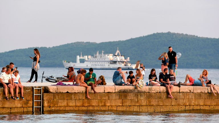 Tourists sit or walk on a pier at sunset in Zadar, on the Adriatic coast on August 6, 2020. - A large number of tourists visited the Zadar Riviera, regardless of the novel coronavirus pandemic. Tourism is very important for Croatia, as almost 20% of GDP comes from it. (Photo by Denis LOVROVIC / AFP) (Photo by DENIS LOVROVIC/AFP via Getty Images)