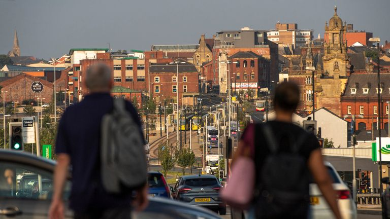 OLDHAM, ENGLAND - AUGUST 13: People walk towards Oldham town centre on August 13, 2020 in Oldham, England. The town is on the brink of a local lockdown after a surge in coronavirus cases has left it the worst affected area in England. (Photo by Anthony Devlin/Getty Images)