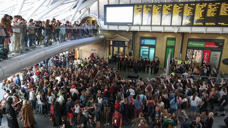 Harry Potter fans gather to watch as the Hogwarts Express appears on the departure board at London King's Cross during Back to Hogwarts Day. The day celebrates the literary moment when Harry Potter started his journey back to Hogwarts each year.