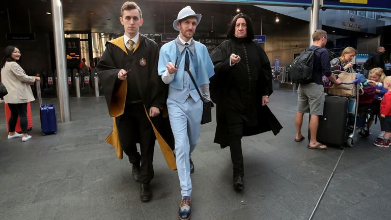 Harry Potter fans George Wells, Rodney Zieseniss and Colin Gilby gather at Platform nine and three quarters as the Hogwarts Express appears on the departure board at London King's Cross during Back to Hogwarts Day. The day celebrates the literary moment when Harry Potter started his journey back to Hogwarts each year.