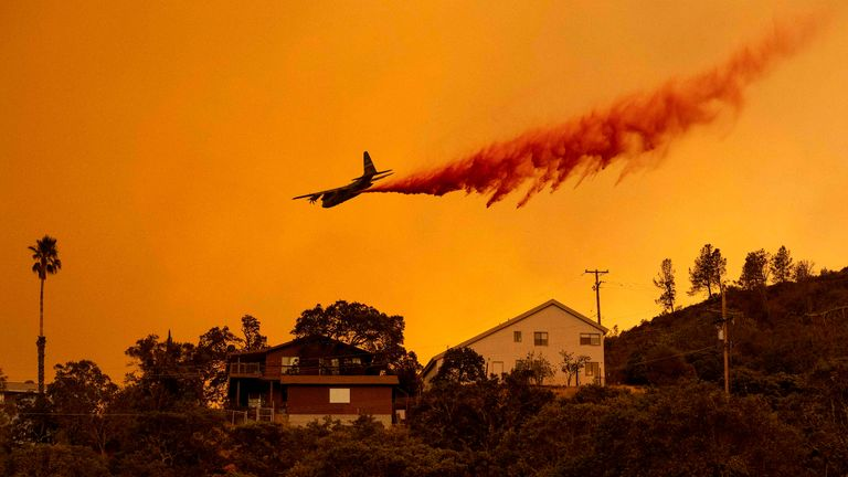 An airplane makes a retardant drop over homes in the Spanish Flat area of Napa, California during the Hennessey fire on August 18, 2020. - As of the late hours of August 18, the Hennessey fire has merged with at least 7 fires and is now called the LNU Lightning Complex fires. Dozens of fires are burning out of control throughout Northern California as fire resources are spread thin. (Photo by JOSH EDELSON / AFP) (Photo by JOSH EDELSON/AFP via Getty Images)