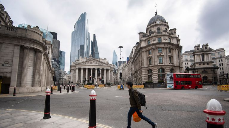 A man walks through a deserted Bank junction in the City of London as the UK continues in lockdown to help curb the spread of the coronavirus.