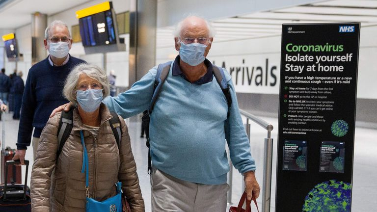 Travellers who had been aboard the Braemar cruise ship, operated by Fred Olsen Cruise Lines, and wearing face masks as a precautionary measure against covid-19, react as they arrive at Heathrow Airport in London on March 19, 2020, after being flown back from Cuba. - The MS Braemar had more than 1,000 people aboard including five confirmed coronavirus cases and more than 50 people in isolation due to showing flu-like symptoms. (Photo by Tolga AKMEN / various sources / AFP) (Photo by TOLGA AKMEN/Tolga Akmen/AFP via Getty Images)