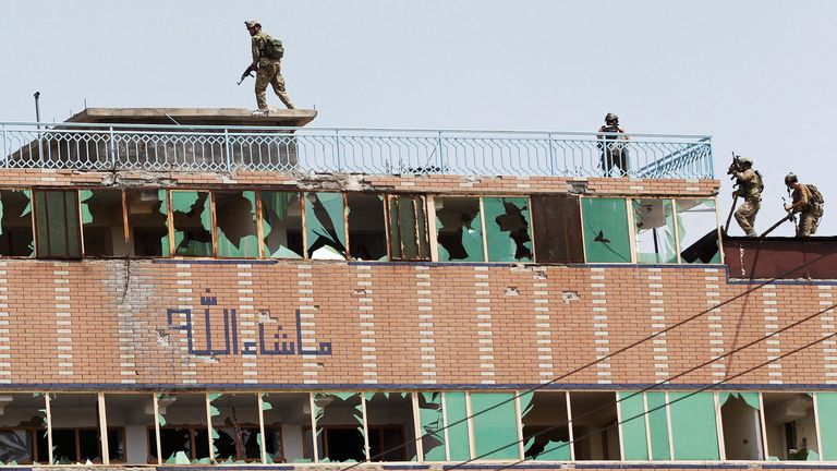 Afghan security forces take position on a building in Jalalabad where militants were thought to be hiding