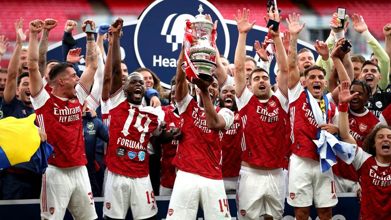Arsenal's Pierre-Emerick Aubameyang (left) is helped by teammates after dropping the FA Cup trophy during the Heads Up FA Cup final match at Wembley Stadium, London