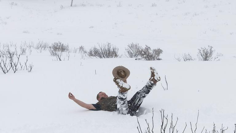 Tourist Barry Mckowski, who is seeing snow for the first time, buries himself in the snow on August 23, 2020 near the small Snowy Mountains town of Adaminaby, Australia