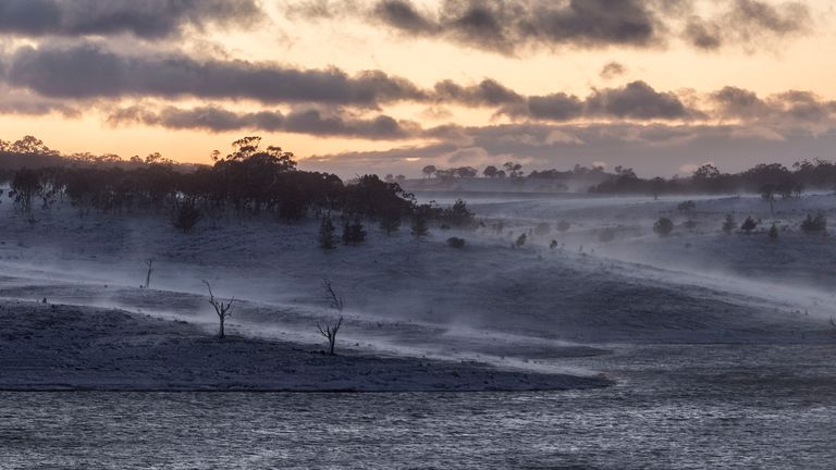A heavy blanket of snow is seen at dawn over Lake Eucumbene near Old Adaminaby