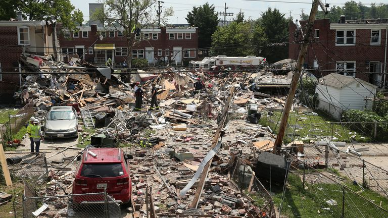 First responders dig through the rubble of three houses demolished by a gas explosion in Baltimore