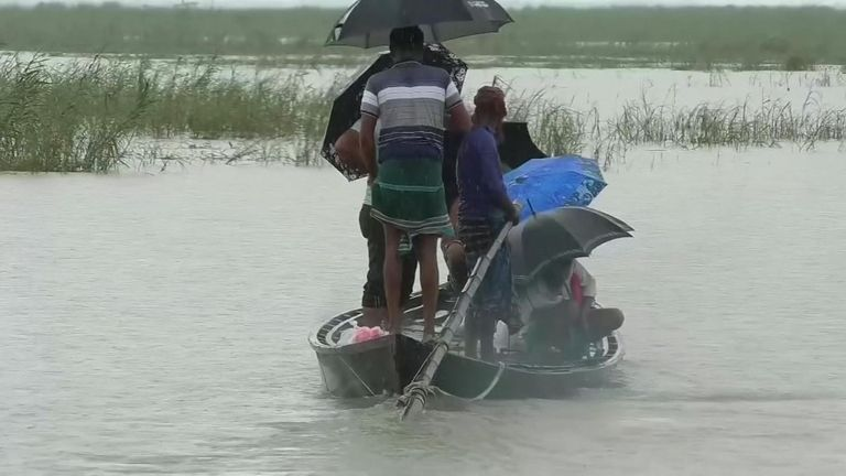 People use a canoe to escape floodwaters in Bangladesh