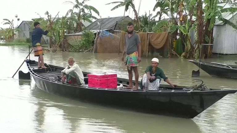 Family evacuate their home by boat in Bangladesh floods