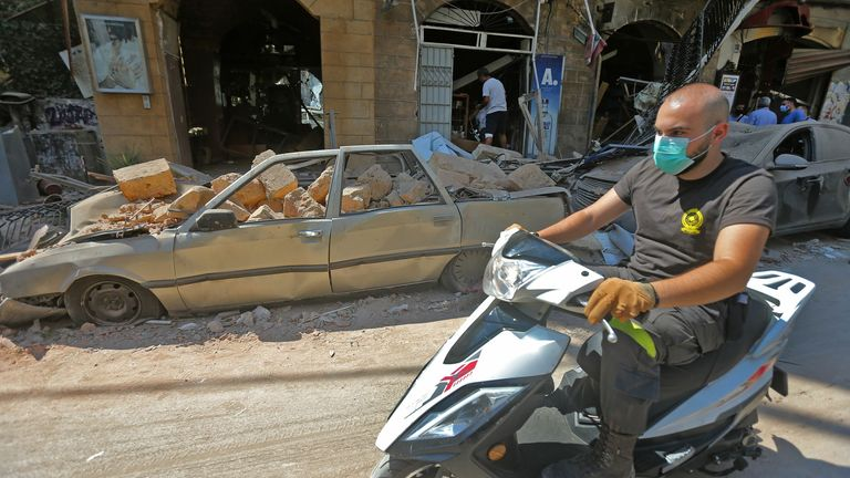 A man wearing a face mask rides his motorbike past damaged cars and shops in Beirut