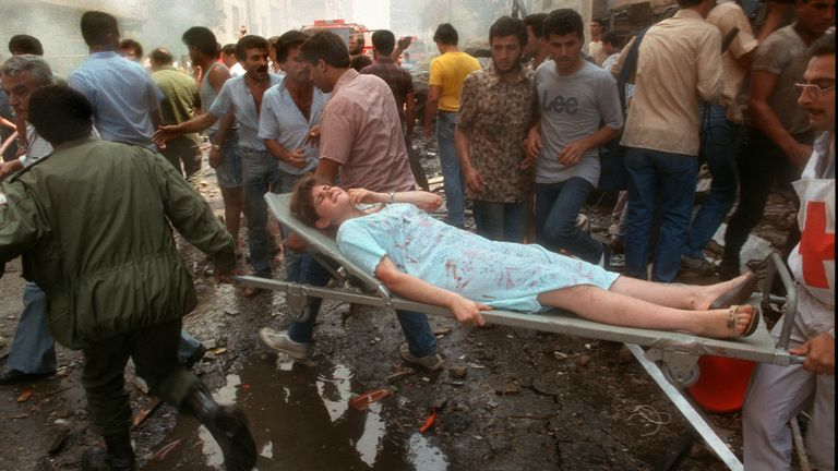Rescuers extract on a stretcher a wounded girl from a building during the civil war in 1985