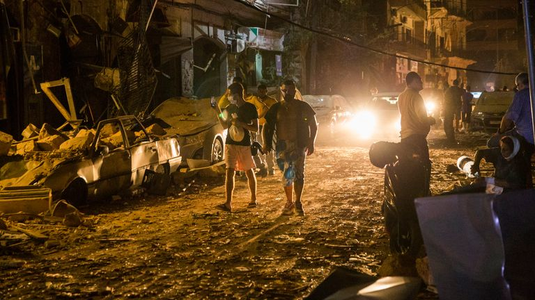 People walk on a street covered in debris following the explosion