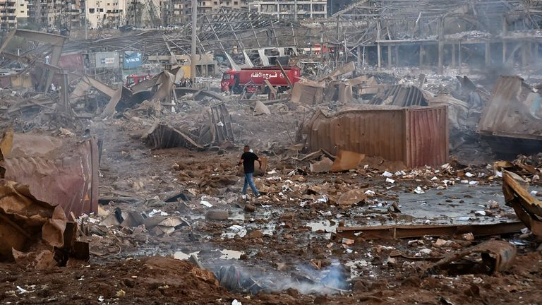A man walks across the rubble near the scene of the explosion in Beirut