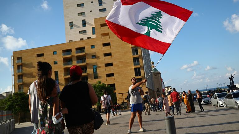 A demonstrator waves a Lebanese flag during a protest in Beirut, Lebanon