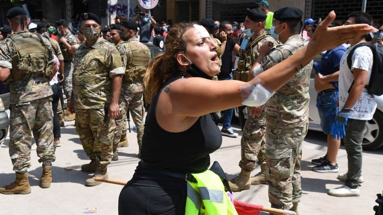 An injured woman protested against the government as Emmanuel Macron visited one of the worst-hit neighbourhoods