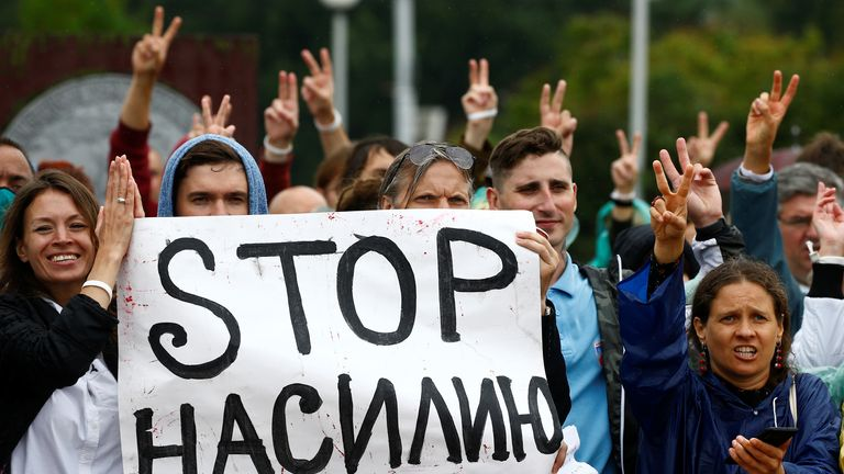 """People, including employees of Minsk Tractor Works, gather near the plant to protest against presidential election results and to demand re-election in Minsk, Belarus August 19, 2020. The placard reads: """"Stop the violence"""". REUTERS/Vasily Fedosenko"""