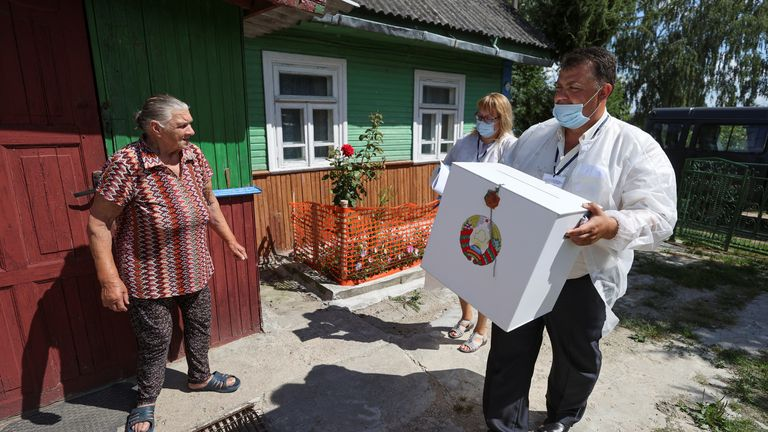 Members of an electoral commission visit local residents during the presidential election near Grodno