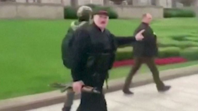 Belarusian President Alexander Lukashenko walks outside the Independence Palace in Minsk carrying a rifle