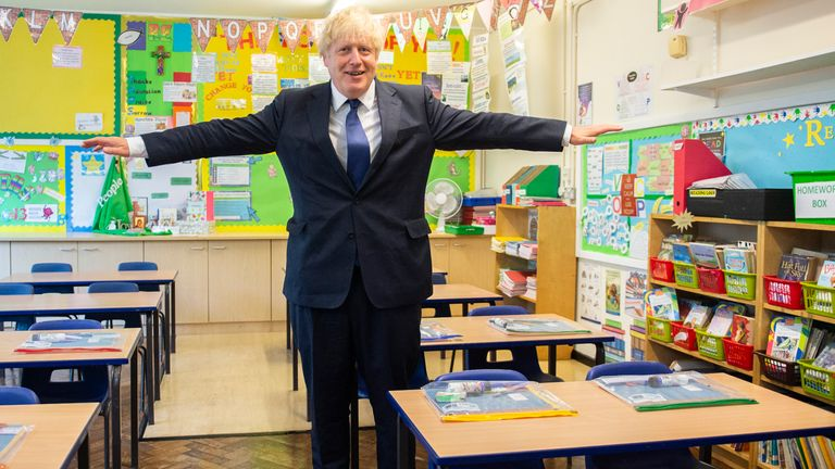 Boris Johnson holds his arms out like an aeroplane, demonstrating the two-metre distancing rule, during his visit to St Joseph's Catholic Primary School in Upminster, east London