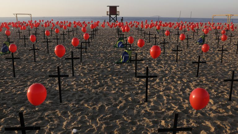 A woman jogs past crosses and balloons placed by members of the NGO Rio de Paz in tribute to the one hundred thousand mortal victims of the coronavirus disease (COVID-19) in the country, at the Copacabana beach in Rio de Janeiro, Brazil August 8, 2020. REUTERS/Ricardo Moraes TPX IMAGES OF THE DAY