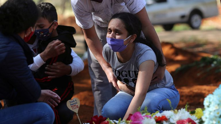 A woman mourns her mother, who died from suspected coronavirus, at a funeral in Sao Paulo