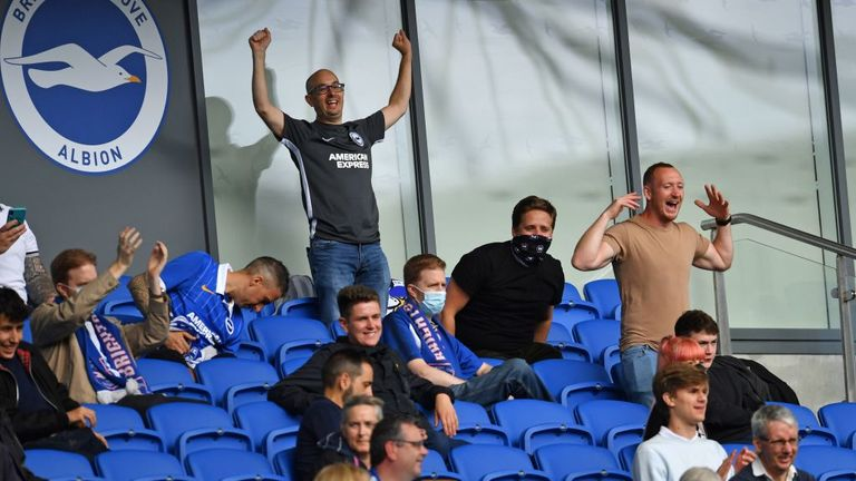 Socially distanced fans cheer a decision in the stands during the pre-season friendly football match between Brighton and Hove Albion and Chelsea at the American Express Community Stadium in Brighton, southern England on August 29, 2020. - The game is a 'pilot' event where a small number of fans will be present on a socially-distanced basis. The aim is to get fans back into stadiums in the Premier League by October. (Photo by Glyn KIRK / AFP) (Photo by GLYN KIRK/AFP via Getty Images)