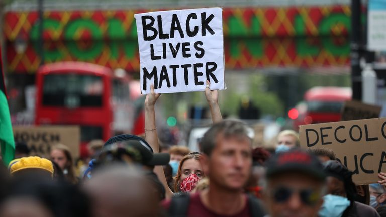 A woman holds a BLM sign in brixton