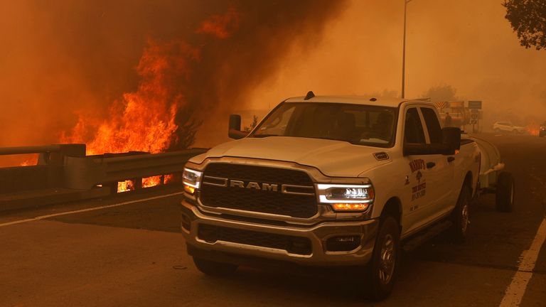 A truck passes flames on a motorway on the outskirts of Vacaville