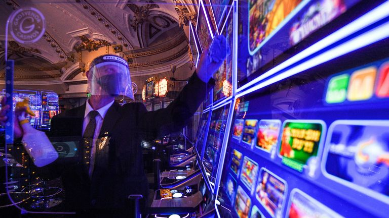 Staff clean screens by the slot machines at The Rialto casino in central London