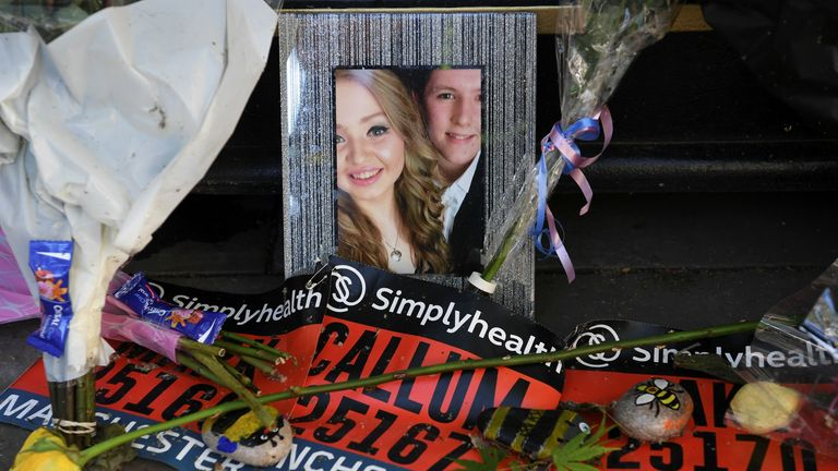 A photograph of victims Liam Curry and Chloe Rutherford is seen amongst floral tributes at the base of a 'tree of hope', planted as a memorial following the Manchester Arena bombing in central Manchester on May 22, 2018, the one year anniversary of the deadly attack. - Prime Minister Theresa May and Prince William will on May 22, 2018 join families of the victims of the Manchester Arena bombing at a commemoration ceremony in the city on the first anniversary of the tragedy. They will attend the