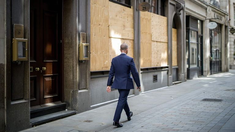 A man walks past a closed and boarded up restaurant in the City of London on August 21, 2020.