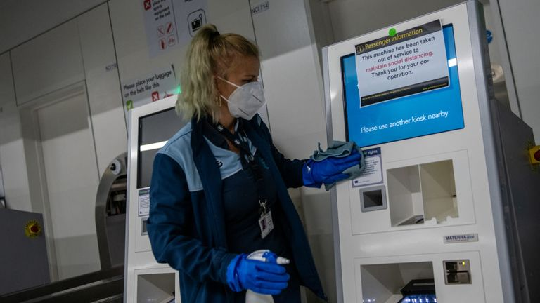 A cleaner is seen wiping down a machine at Gatwick Airport during the pandemic