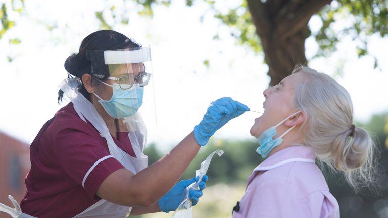 A woman takes a coronavirus swab test