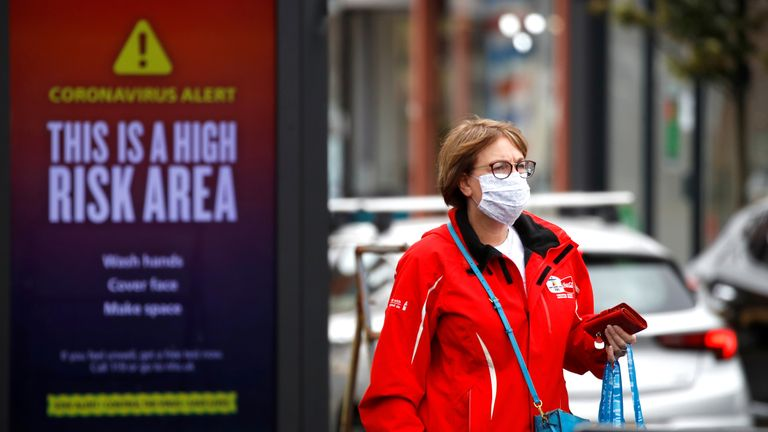 A woman wearing a protective mask walks past a warning sign in Manchester, as the city and the surrounding area faces local restrictions in an effort to avoid a local lockdown being forced upon the area, amid the coronavirus disease (COVID-19) outbreak, Britain, August 1, 2020. REUTERS/Phil Noble