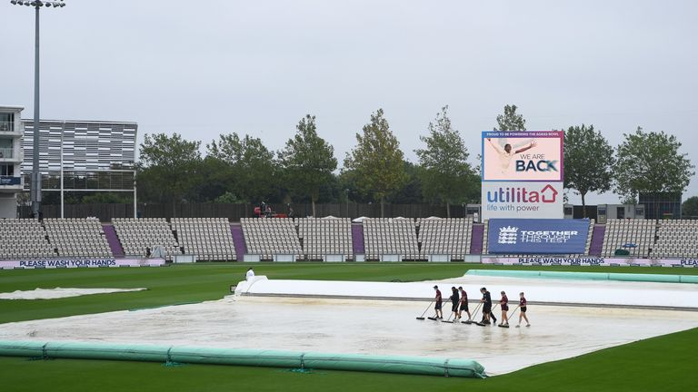 Ground staff prepare to clear water from the covers at the Ageas Bowl in Southampton