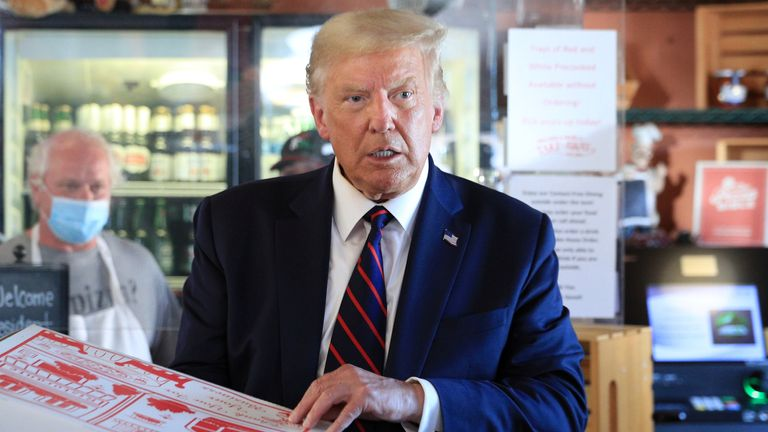 Donald Trump holds a pizza in a box