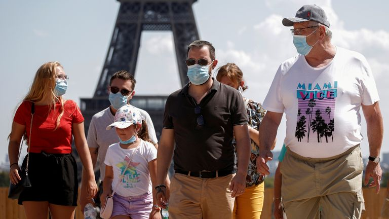 People are seen wearing face masks near the Eiffel Tower in France