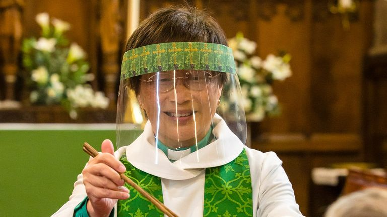 Rev Harrop dons a visor or face mask as a protective measure during her services