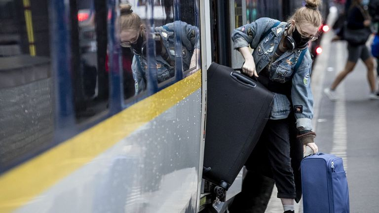 A passenger wearing a protective face mask, carries her luggage as she gets off an Eurostar train at Amsterdam Central Station, on July 9, 2020. - After a stop due to the COVID-19 pandemic caused by the novel coronavirus, the high-speed train between London and Amsterdam runs daily again between the two capitals. (Photo by Sem VAN DER WAL / ANP / AFP) / Netherlands OUT (Photo by SEM VAN DER WAL/ANP/AFP via Getty Images)