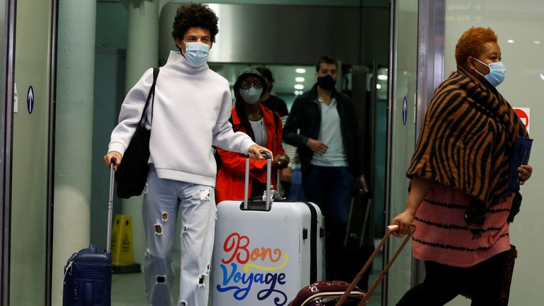 Passengers wearing protective face masks arrive from Paris at the Eurostar terminal at London St Pancras this morning