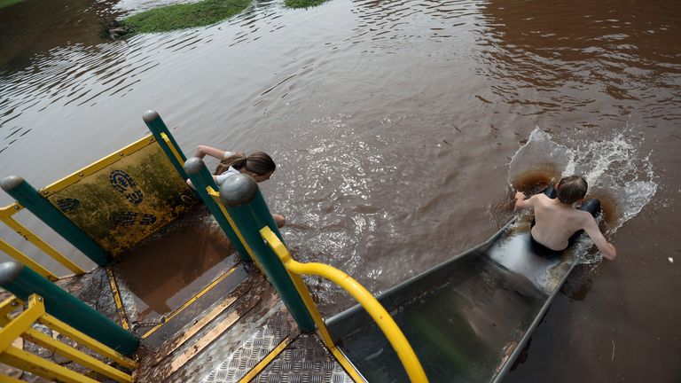 Children play in a flooded park in Newcastle-under-Lyme, Britain August 13, 2020. REUTERS/Carl Recine