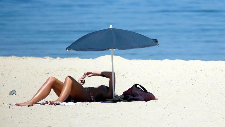 A woman sunbathes on a beach along the Bassin d'Arcachon Sea in Arcachon, southwestern France, as unusually high temperatures hit France, June 21, 2017.   REUTERS/Regis Duvignau