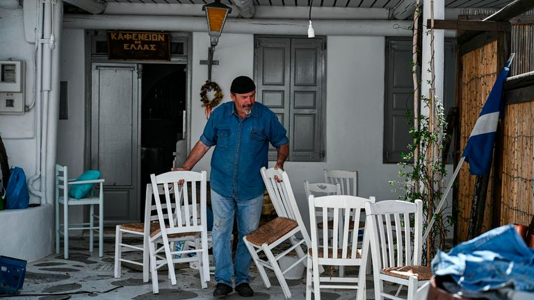 A man moves some chairs as he prepares his cafe for the summer season in the Greek Cycladic island of Mykonos, on May 13, 2020. - In Mykonos, at the start of the tourist season, the image is striking: the posh island traditionally crowded with wealthy foreigners has turned into a ghost island, offering visitors deserted alleys, boarded up shops, restaurants and abandoned hotels. (Photo by ARIS MESSINIS / AFP)